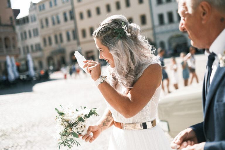 Braut winkt auf Marktplatz vor Standesamt
